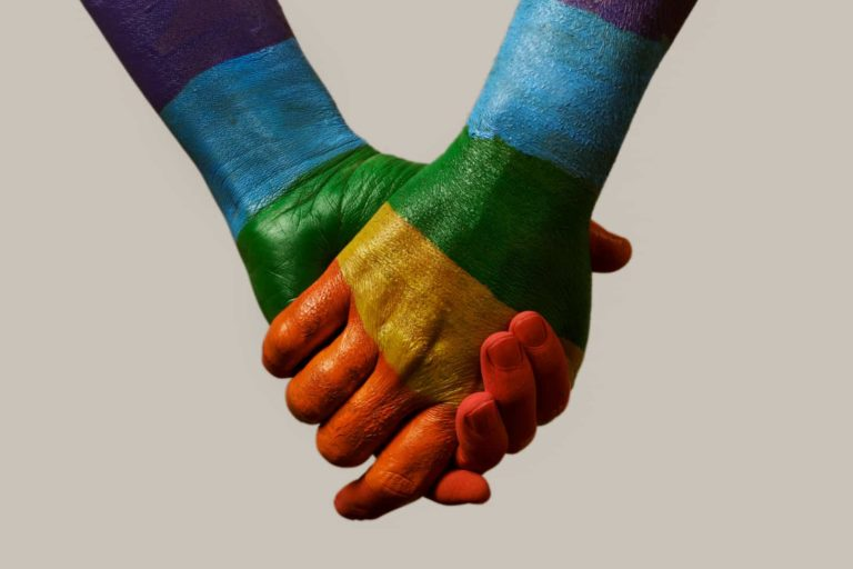 two people holding hands covered in rainbow colours
