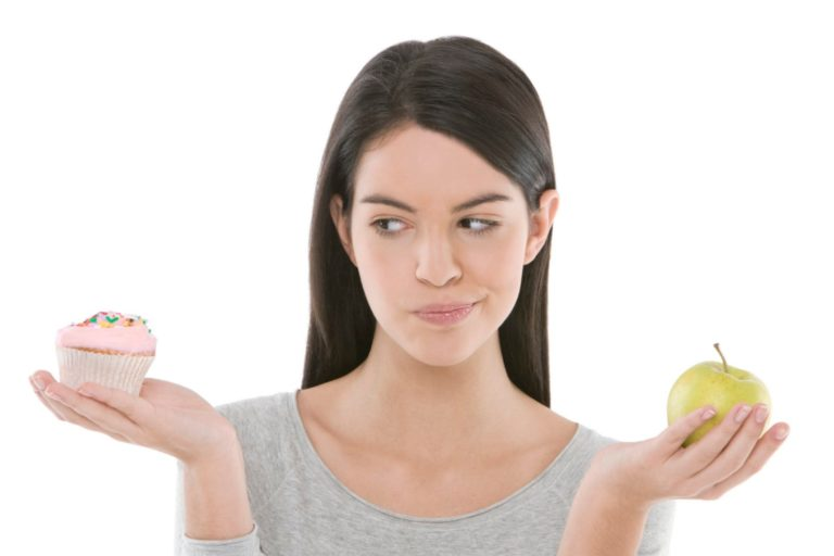 a woman contemplating a cupcake or apple