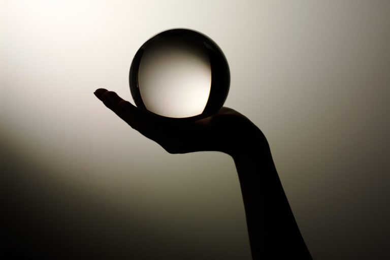 silhouette of a hand holding a glass ball