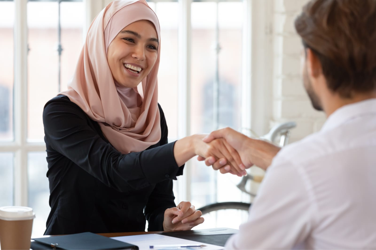 A woman and man shaking hands during a meeting